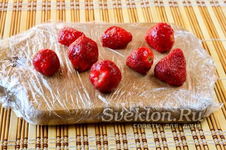 разделочную доску обернуть пищевой пленкой и разложить на ней клубнику, отправить ягоду в морозилку